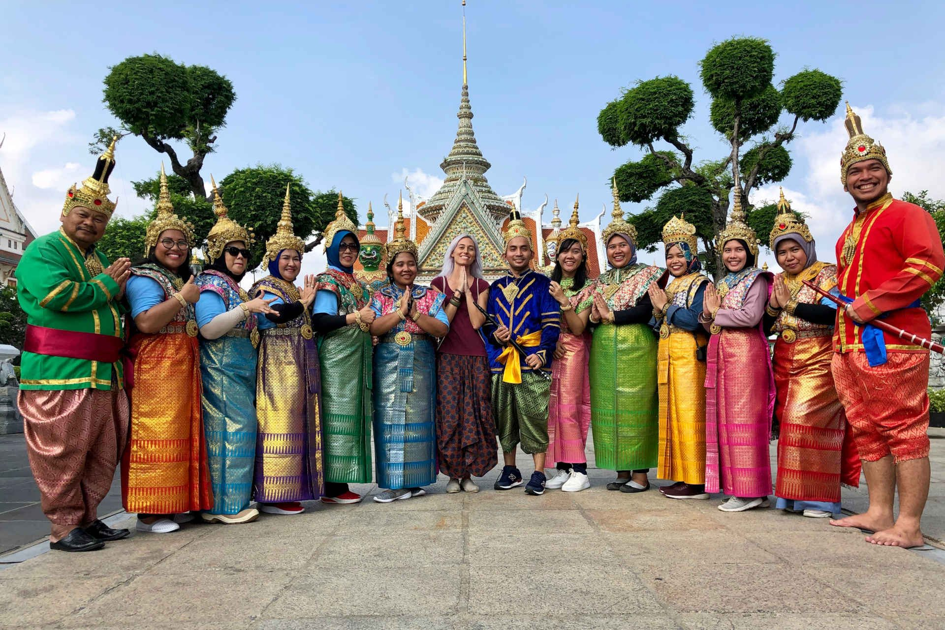 A group of Indonesian tourists posing in traditional Thai costumes at Wat Arun